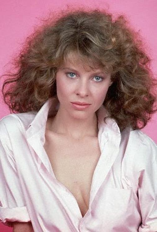 1981 --- 1981- Picture shows actress, Kate Capshaw, posing in front of a pink background wearing a white button-down with the sleeves rolled up. --- Image by © Lynn Goldsmith/CORBIS